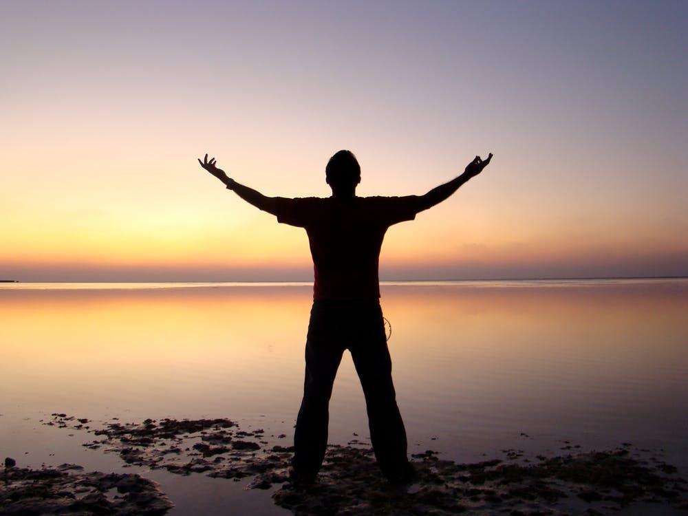 Levenscoach - Man op strand met armen wijd uitgestrekt de Nieuwetijdcoach
