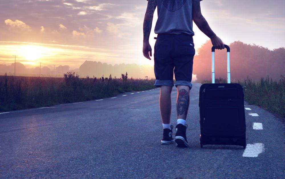 Man op weg met reiskoffer. De nieuwetijdcoach